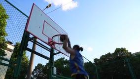 Sluit omhoog lengte van een speler die van het jonge mensenbasketbal en in openlucht op het lokale hof opleiden uitoefenen jonge  stock footage