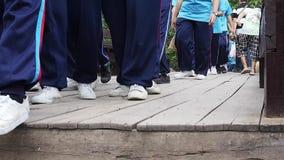 Sluit omhoog lengte van niet geïdentificeerde menigte lopend over houten brug stock videobeelden