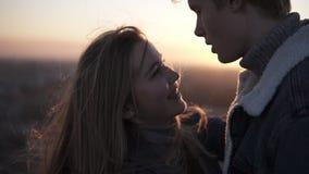 Sluit omhoog lengte van romantisch jong paar die face to face zich backlit door de zon met gloedeffect terwijl status bevinden stock footage