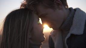 Sluit omhoog lengte van romantisch jong paar face to face backlit door de zon met gloedeffect terwijl status op het dak stock footage