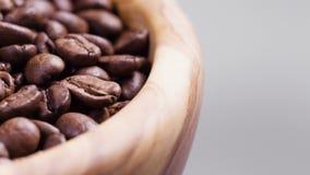 Sluit omhoog lengte van roterende geroosterde koffiebonen in houten kom stock footage