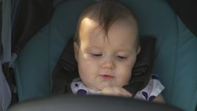 Sluit omhoog: leuk meisje die en bij camerazitting bekijken glimlachen in blauwe kinderwagen - scène van de de kleurenzomer van f stock video