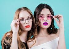 Sluit omhoog levensstijlportret van twee aantrekkelijke meisjes op blauwe achtergrond Brunette en blonde met ronde glazen, met he royalty-vrije stock afbeelding