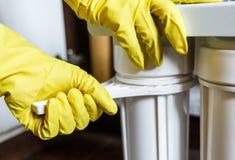 Sluit omhoog Loodgieter in de gele filters van het de veranderingenwater van huishoudenhandschoenen De filterpatronen van het her stock foto's
