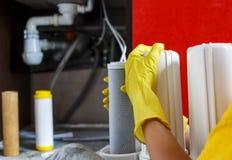 Sluit omhoog Loodgieter in de gele filters van het de veranderingenwater van huishoudenhandschoenen De filterpatronen van het her royalty-vrije stock foto
