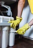Sluit omhoog Loodgieter in de gele filters van het de veranderingenwater van huishoudenhandschoenen De filterpatronen van het her royalty-vrije stock fotografie
