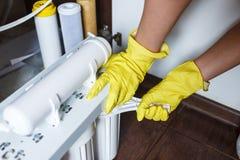 Sluit omhoog Loodgieter in de gele filters van het de veranderingenwater van huishoudenhandschoenen De filterpatronen van het her royalty-vrije stock foto's