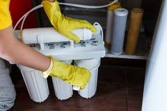 Sluit omhoog Loodgieter in de gele filters van het de veranderingenwater van huishoudenhandschoenen De filterpatronen van het her royalty-vrije stock afbeeldingen
