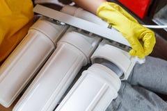 Sluit omhoog Loodgieter in de gele filters van het de veranderingenwater van huishoudenhandschoenen De filterpatronen van het her stock afbeeldingen