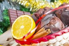 Sluit omhoog maffins, sinaasappelen en chocolade op Kerstboomachtergrond stock afbeeldingen