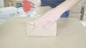 Sluit omhoog man handen inpakkend dozen sellotape in de drukindustrie, vooraanzicht stock footage