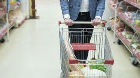 Sluit omhoog man karretje van handenbroodjes met product in het uitwisselen van vloer van supermarkt, steadicam schot stock footage