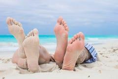 Sluit omhoog mannelijke en vrouwelijke voeten op wit zand Stock Afbeeldingen