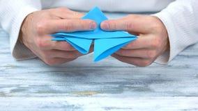 Sluit omhoog mannelijke handen die origamicijfer vouwen royalty-vrije stock afbeelding