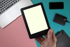 Sluit omhoog mannelijke handen houdend een tablet op de achtergrond van de bureaulijst stock afbeelding