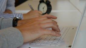 Sluit omhoog mannelijke handen typend op een notitieboekjetoetsenbord De vrouwelijke handen die van ` s met een pen op rug schrij stock videobeelden