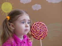 Sluit omhoog meisje bekijkt verrast de lolly Stock Foto