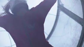 Sluit omhoog meisjes skydiver vliegen in lucht in windtunnel Het vliegen in een windtunnel stock footage
