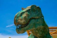 Sluit omhoog mening aan een openen-mondhoofd van dinosaurus op een blauwe hemelachtergrond royalty-vrije stock foto's