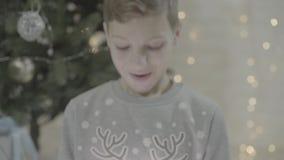 Sluit omhoog mening over de gelukkige opgewekte jongensjong geitje het openen doos van de Kerstmis huidige die gift in ontzagzitt stock videobeelden