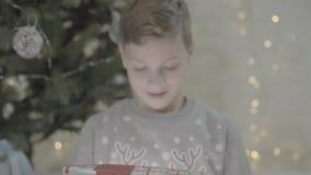 Sluit omhoog mening over de opgewekte gelukkige jongensjong geitje het openen doos van de Kerstmis huidige die gift in ontzagzitt stock footage