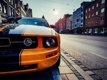 Sluit omhoog mening over een oranje en zwart mustang royalty-vrije stock foto's