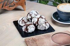 Sluit omhoog mening over eigengemaakte chocoladekoekjes op zwart bord met koffie stock fotografie