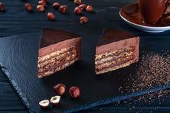 Sluit omhoog mening over gesneden hazelnootcake met cacao op een zwarte achtergrond en een plaat royalty-vrije stock afbeelding