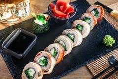 Sluit omhoog mening over reeks van sushibroodje Broodje van Californië met paling, avocado en kaviaar diende op zwarte steen op h royalty-vrije stock afbeeldingen