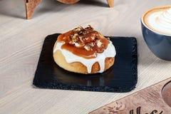 Sluit omhoog mening over vers eigengemaakt cinnabonbroodje met het toping van karamel en noten stock fotografie