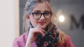 Sluit omhoog mening van aantrekkelijke jonge vrouw die in elegante uitrusting, in het venster kijken, dan draaiend naar de camera stock video