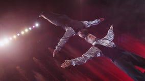 Sluit omhoog mening van acrobaten die handeling maken met tegen kleurrijke fonteinen, Moskou, Rusland