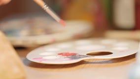 Sluit omhoog mening van artistiek palet op de houten lijst De kunstenaar mengt de verf op het palet Het creatieve werk, art. stock video