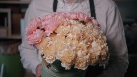 Sluit omhoog mening van bloemist die bloemsamenstelling voorbereiden op het werk, boeket van rozenpeone en sering voor valentijns stock video