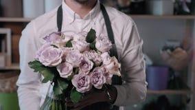 Sluit omhoog mening van bloemist die bloemsamenstelling voorbereiden op het werk, boeket van rozenpeone en sering voor valentijns stock videobeelden