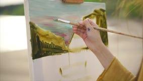 Sluit omhoog mening van canvas en onvolledig beeld Vrouwenschilder stock videobeelden