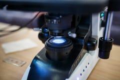 Sluit omhoog mening van de drukcilinder en de dia van microscooplenzen stock afbeelding