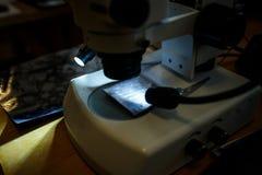 Sluit omhoog mening van de drukcilinder en de dia van microscooplenzen stock afbeeldingen