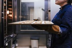 Sluit omhoog mening van de holdingsrek van de vrouwenholding van snoepjes in een bakkerij royalty-vrije stock foto's