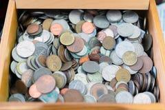 Sluit omhoog mening van de verschillende muntstukken van landen in een houten doos Diverse achtergrond van metaalmuntstukken stock afbeelding