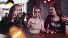 Sluit omhoog mening van drie meisjesvrienden, omhoog toejuichend en het drinken alcoholcocktails die in de club lachen babbelen h stock video