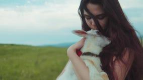 Sluit omhoog mening van een het jonge mooie vrouwenholding, kussen en het petting wit geitjong geitje Houdend van aard, koester a stock video