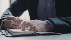 Sluit omhoog mening van een jonge zakenman die op de telefoon spreken, en nota's nemen Zijnd bezige, actieve levensstijl Het beha stock videobeelden
