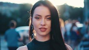 Sluit omhoog mening van een mooie blauw-eyed donkerbruine vrouw die zich in het heldere zonlicht, in de overvolle stadsstraat bev stock videobeelden