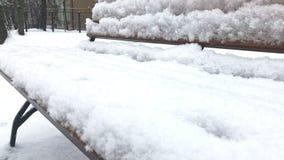 Sluit omhoog mening van een sneeuw de winterbank in een park, valt de sneeuw en onherkenbare mensen die door op achtergrond lopen stock footage