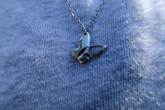 Sluit omhoog mening van een vlinder-vorm halsband bij de borst van een vrouw stock foto