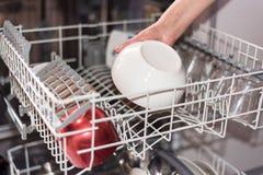 Sluit omhoog mening van een woman'shand die de afwasmachine laden Shallo Royalty-vrije Stock Afbeeldingen