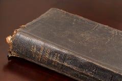 Sluit omhoog mening van een zeer oude familiebijbel die op lijst rust Royalty-vrije Stock Foto