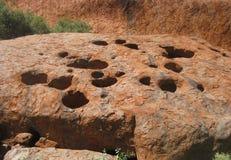 Sluit omhoog mening van gaten in de rots van de Uluru-basisgang stock afbeeldingen