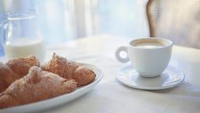Sluit omhoog mening van gediende melk, knapperige croissants en hete koffie op de lijst Ochtend routine, perfect ontbijt het Fran stock video